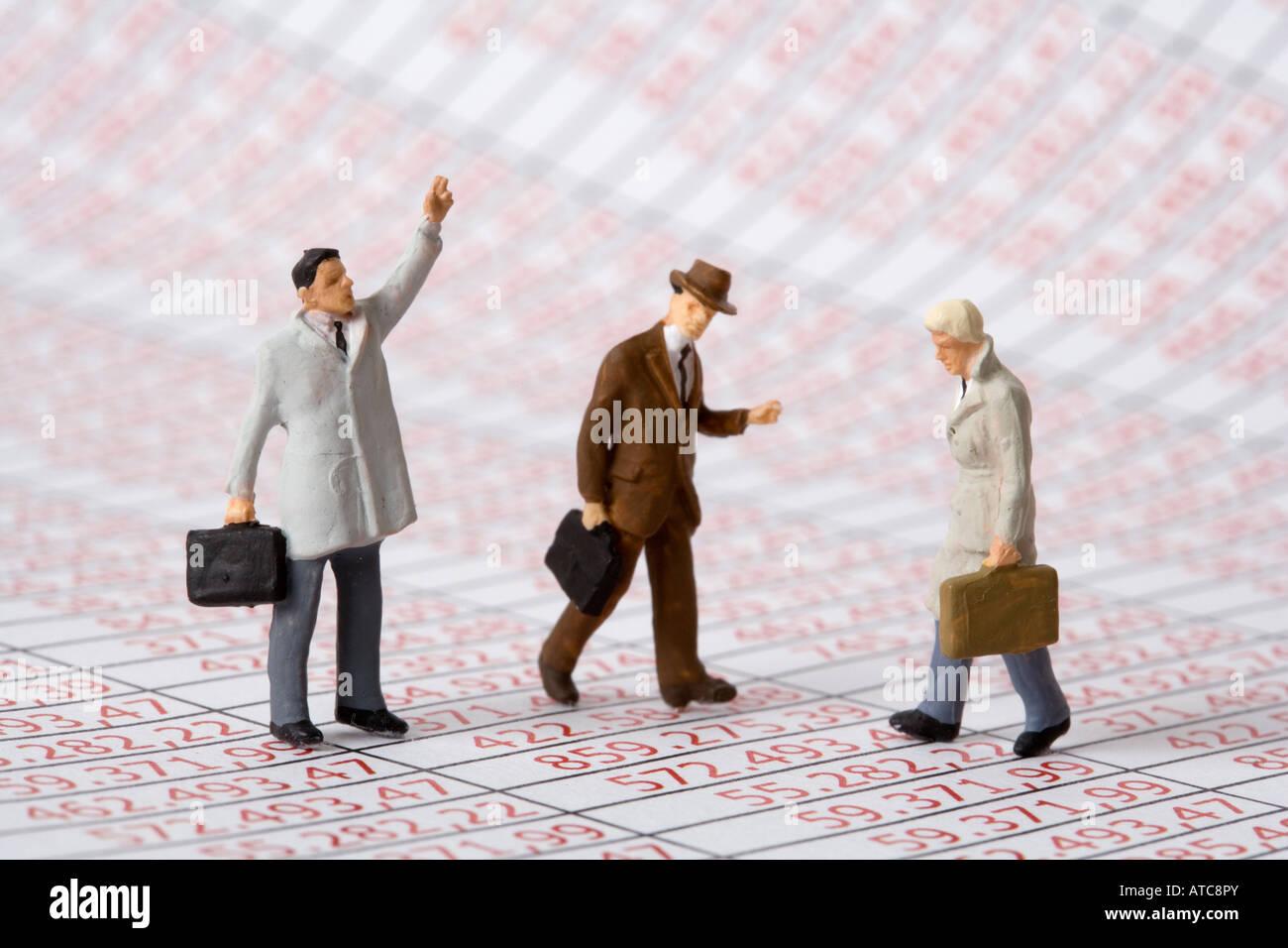 Les figures d'hommes d'affaires sur des colonnes de chiffres symbole manager fraude fiscale etc. Photo Stock