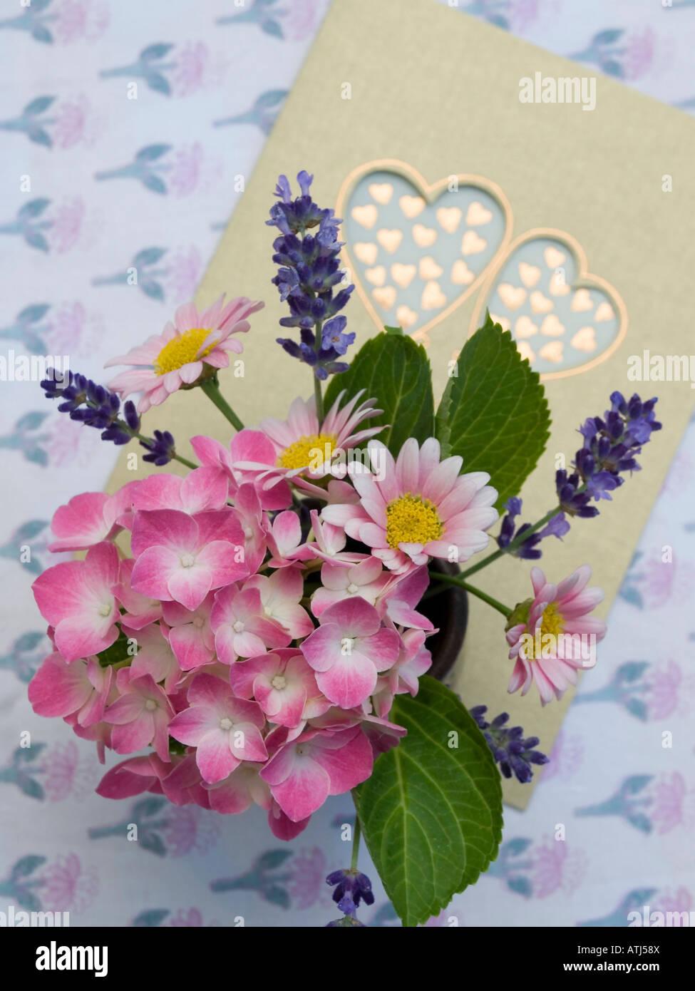 Message d'amour avec carte postale avec deux coeurs et petit bouquet bouquet de fleurs en rose Photo Stock