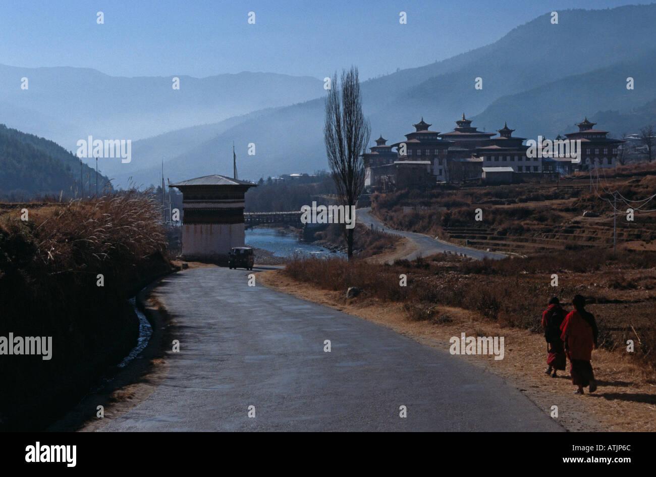 Deux moines bouddhistes à marcher vers Tashichho Dzong (Thimphu Dzong) dans la région de Misty vallée rurale, le Bhoutan, l'Asie du Sud Photo Stock