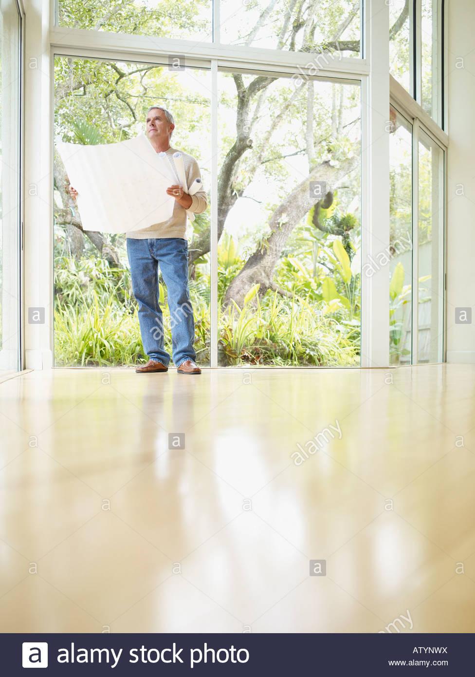 L'homme à l'intérieur par de grandes fenêtres à la recherche des plans à Photo Stock
