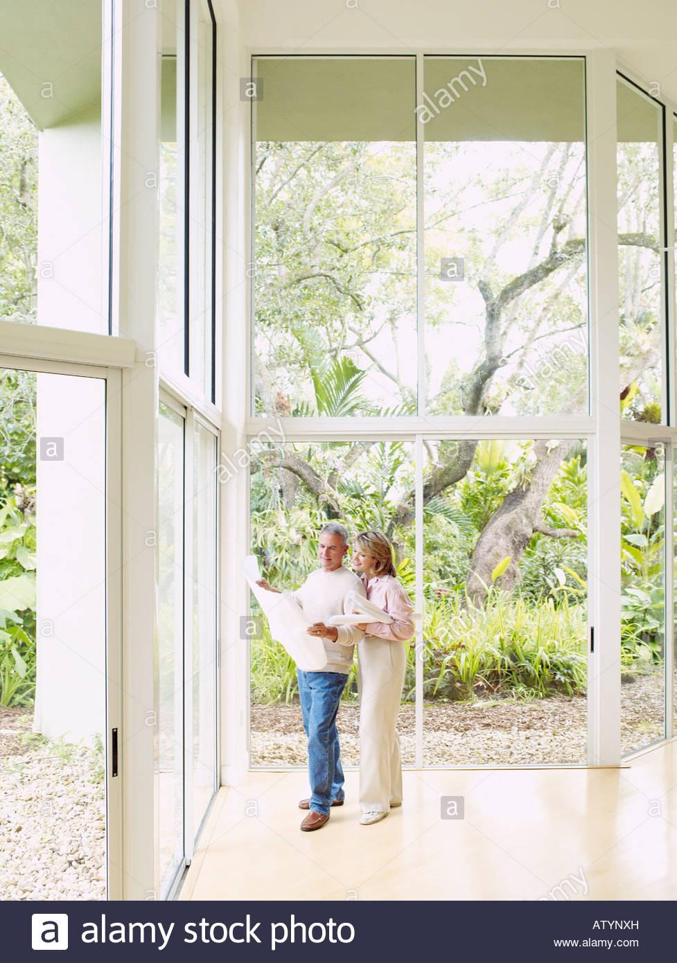 Couple à l'intérieur par de grandes fenêtres à la recherche des plans à Photo Stock