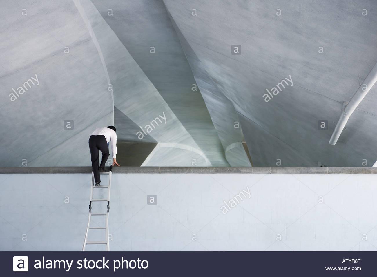 Homme d'affaires à l'intérieur à l'aide de l'échelle à grimper sur la structure Photo Stock