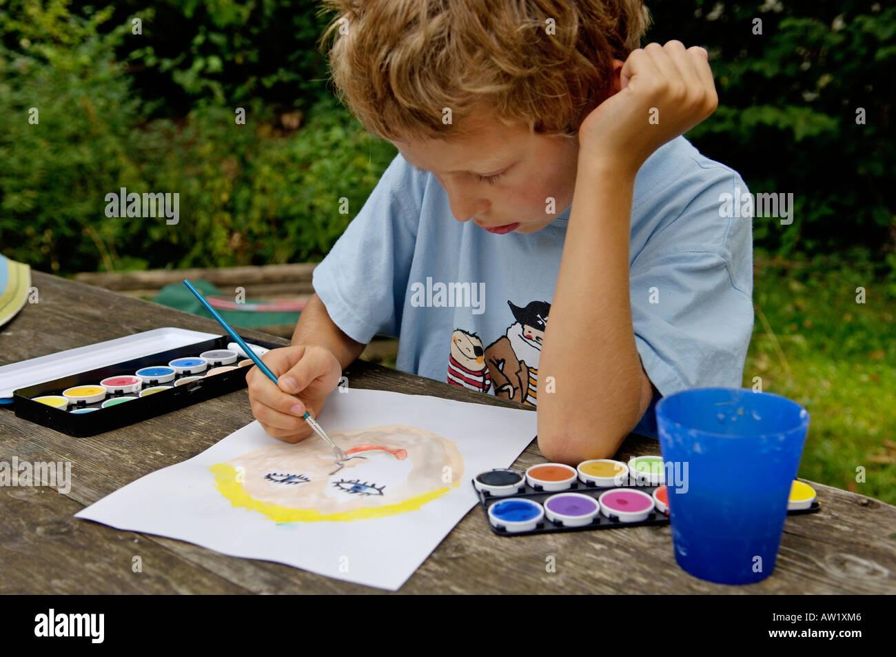 Garçon de neuf ans la peinture d'une photo avec des couleurs de l'eau Photo Stock