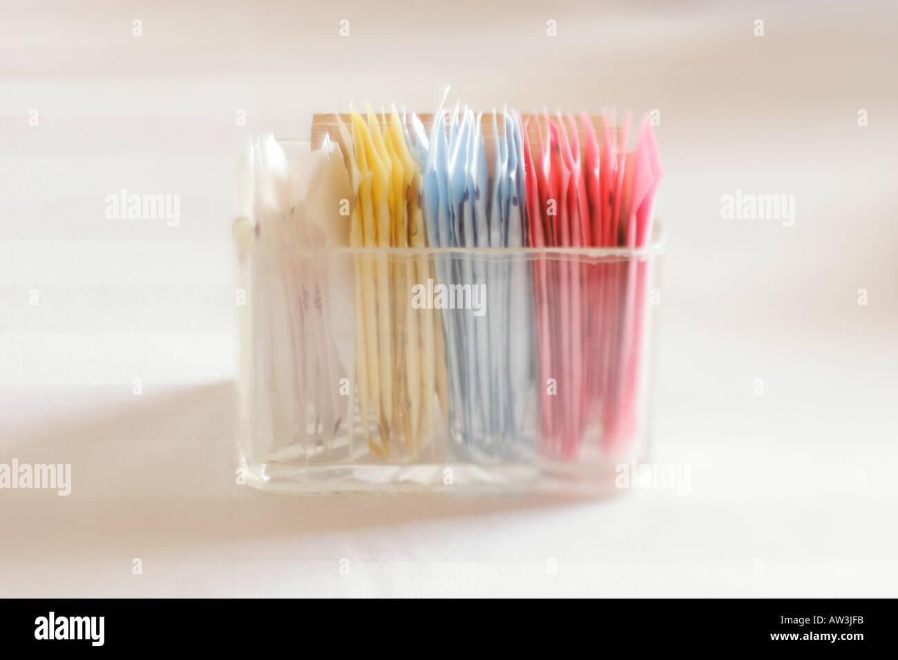 Les paquets de sucre et d'édulcorant artificiel dans des contenants de verre Photo Stock