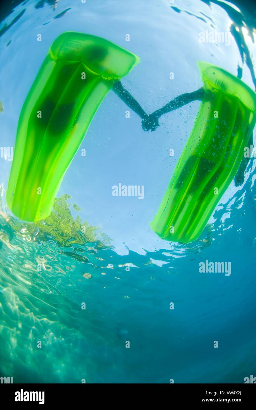 Un couple sur deux radeaux vert tenant la main tourné sous l'eau Photo Stock
