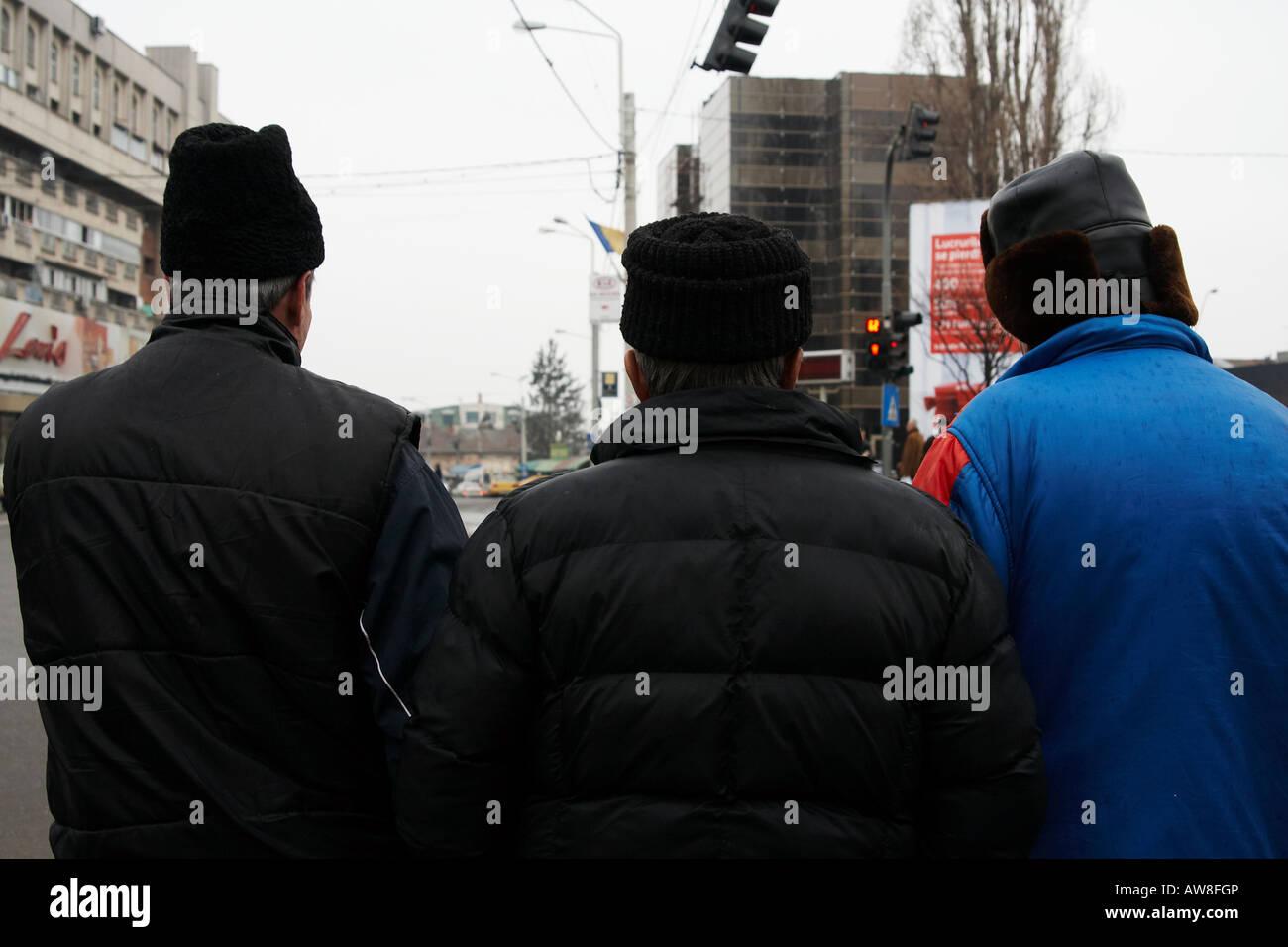 Scène urbaine avec 3 vieux paysans hommes en noir ou formes différentes vue de l'arrière Craiova Photo Stock