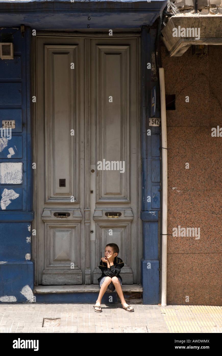 Enfant de la rue assis par des portes à Montevideo, Uruguay Photo Stock