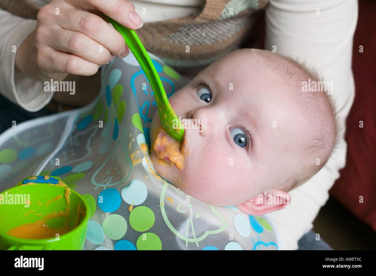 Un ffive mois bébé garçon essaie de la nourriture solide pour la première fois Photo Stock