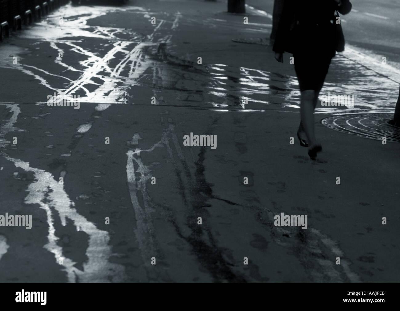 Femme marche sur le trottoir avec des traînées humides, partie inférieure Photo Stock