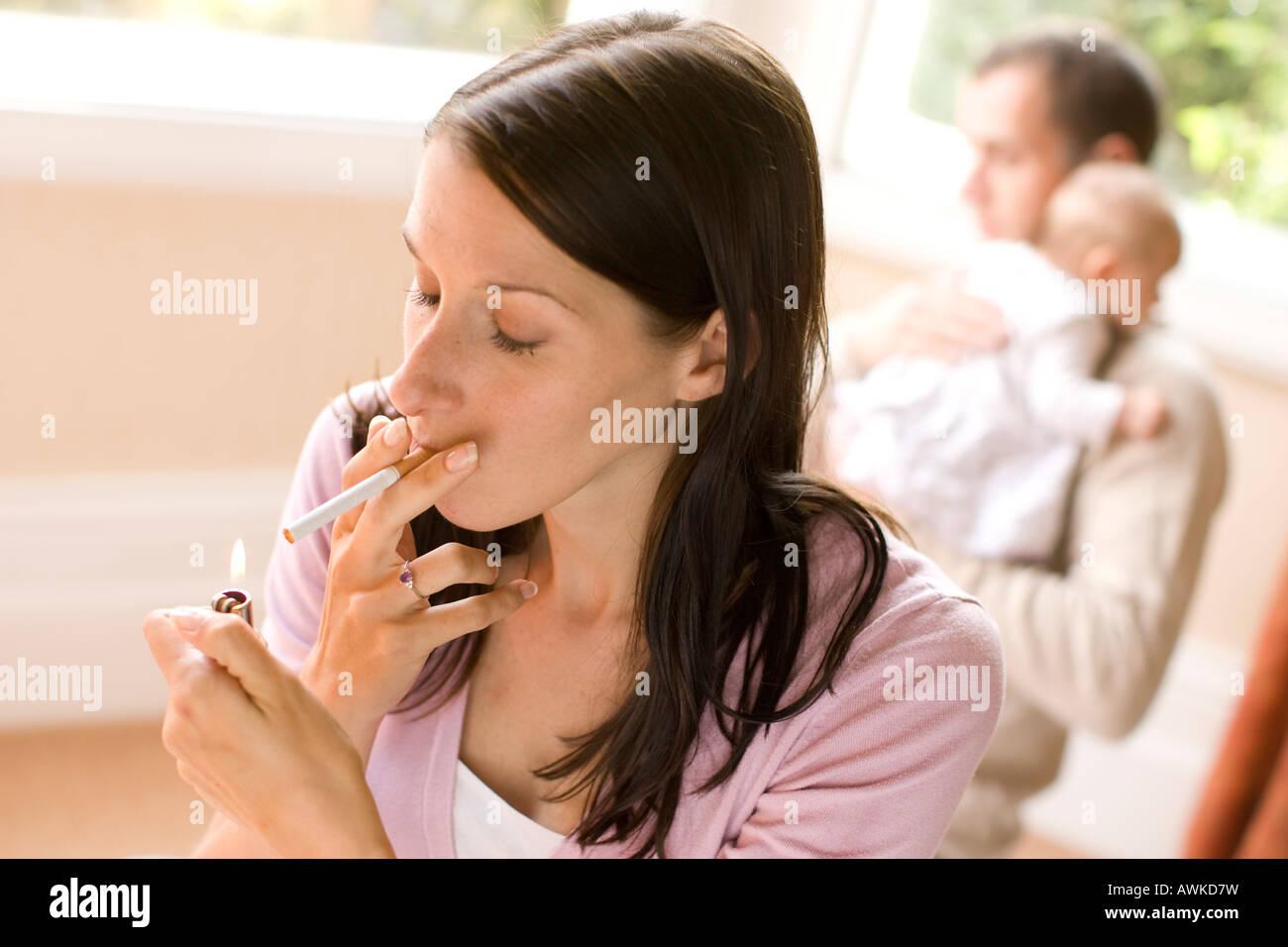 Alors que le tabagisme de la mère père apaise bébé Photo Stock