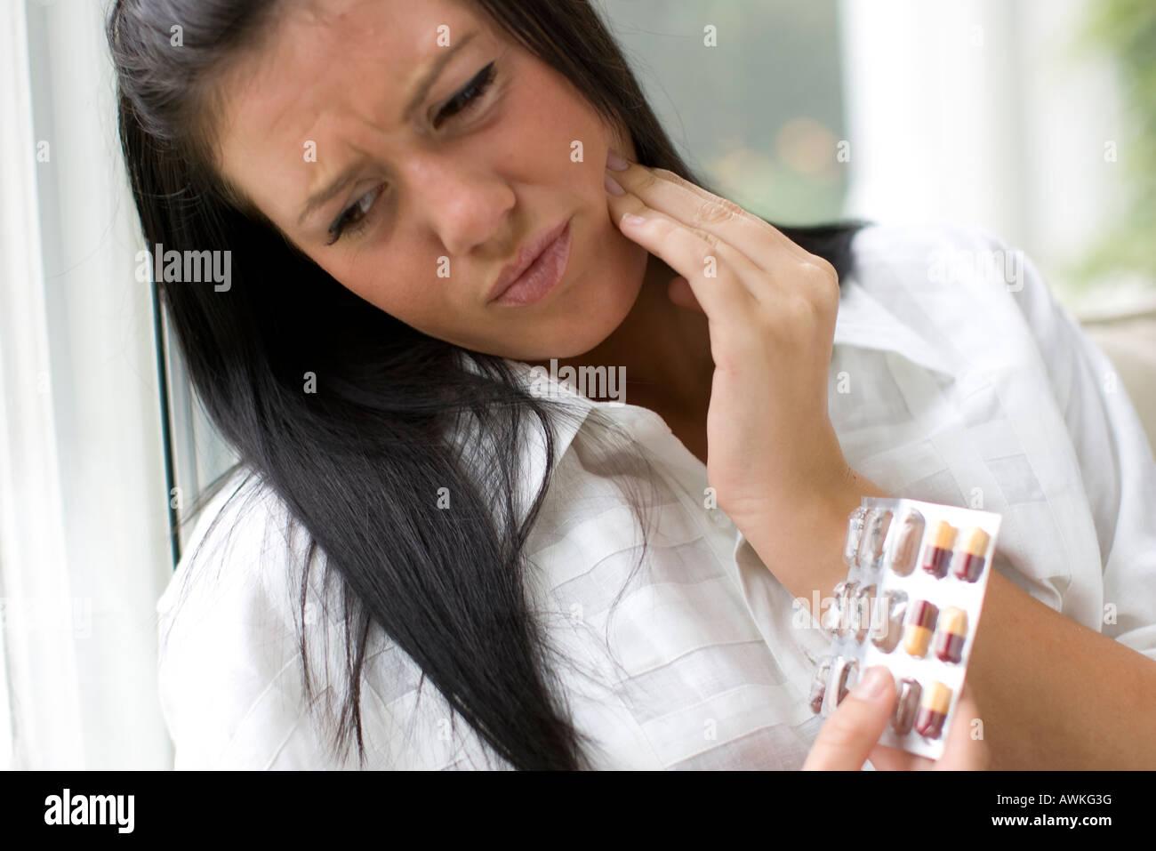 Femme avec des dents et des pilules Banque D'Images