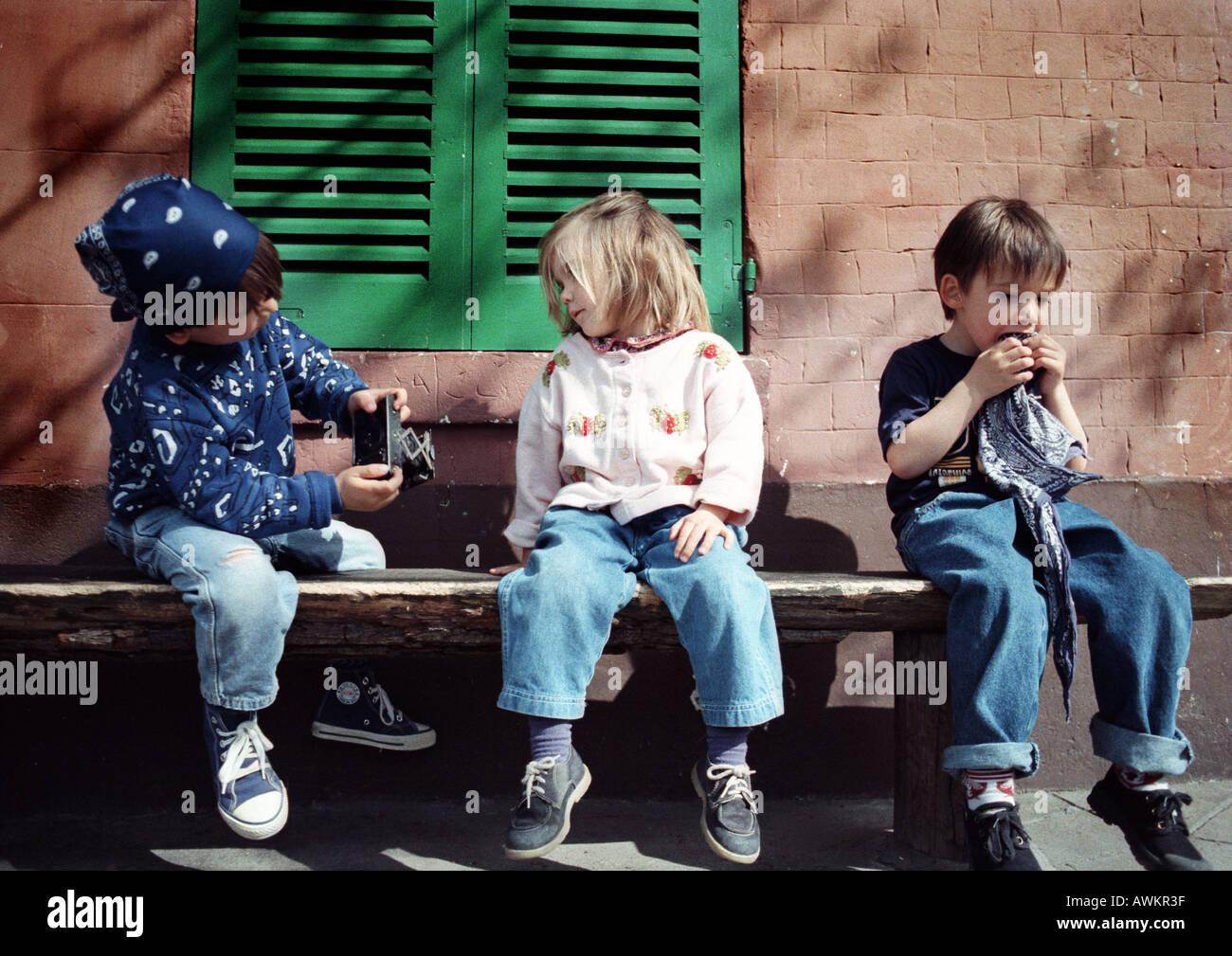 Les enfants assis sur un banc Banque D'Images