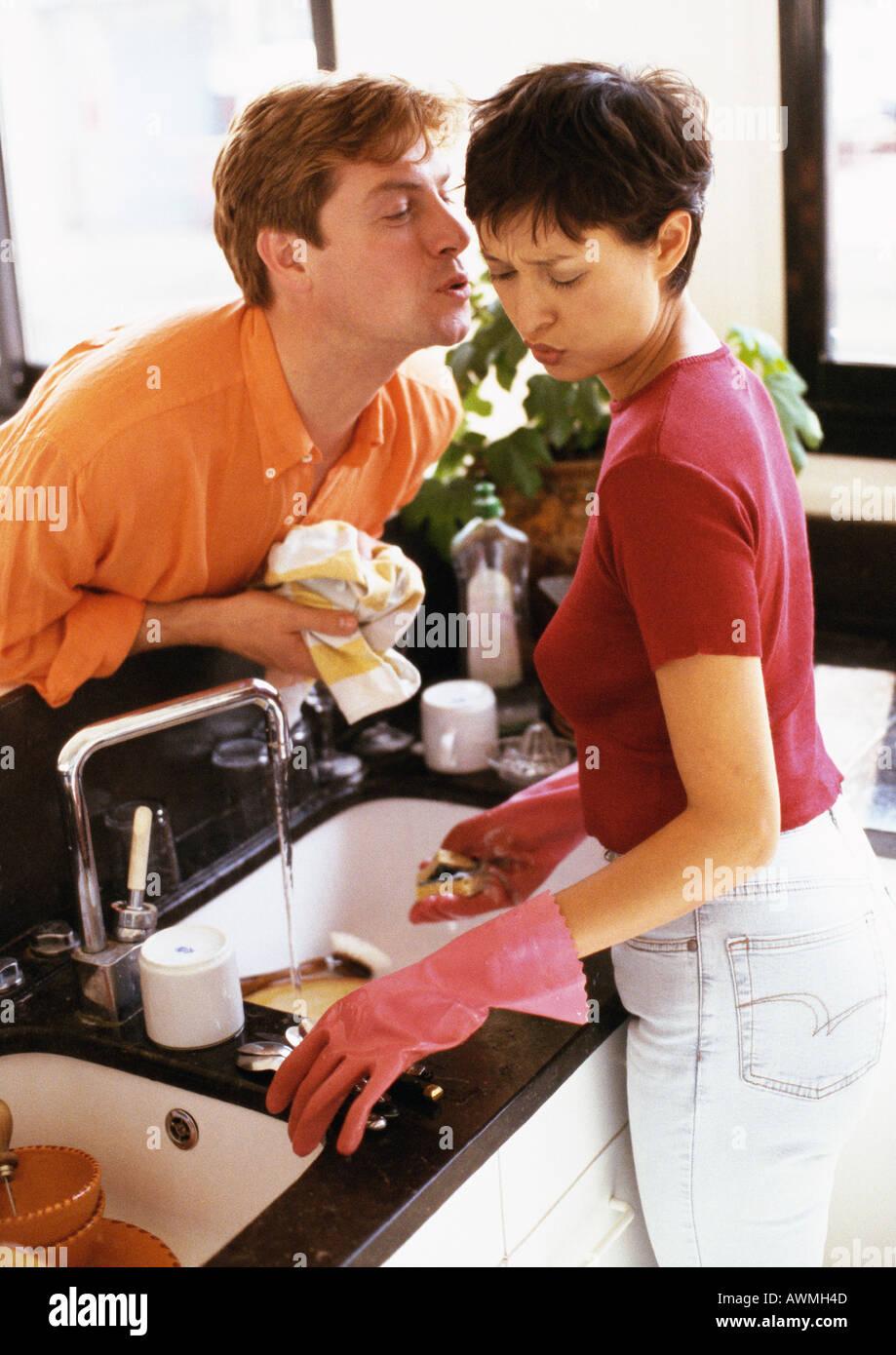 Woman washing dishes, penché au-dessus de l'homme à l'encontre de l'embrasser Banque D'Images