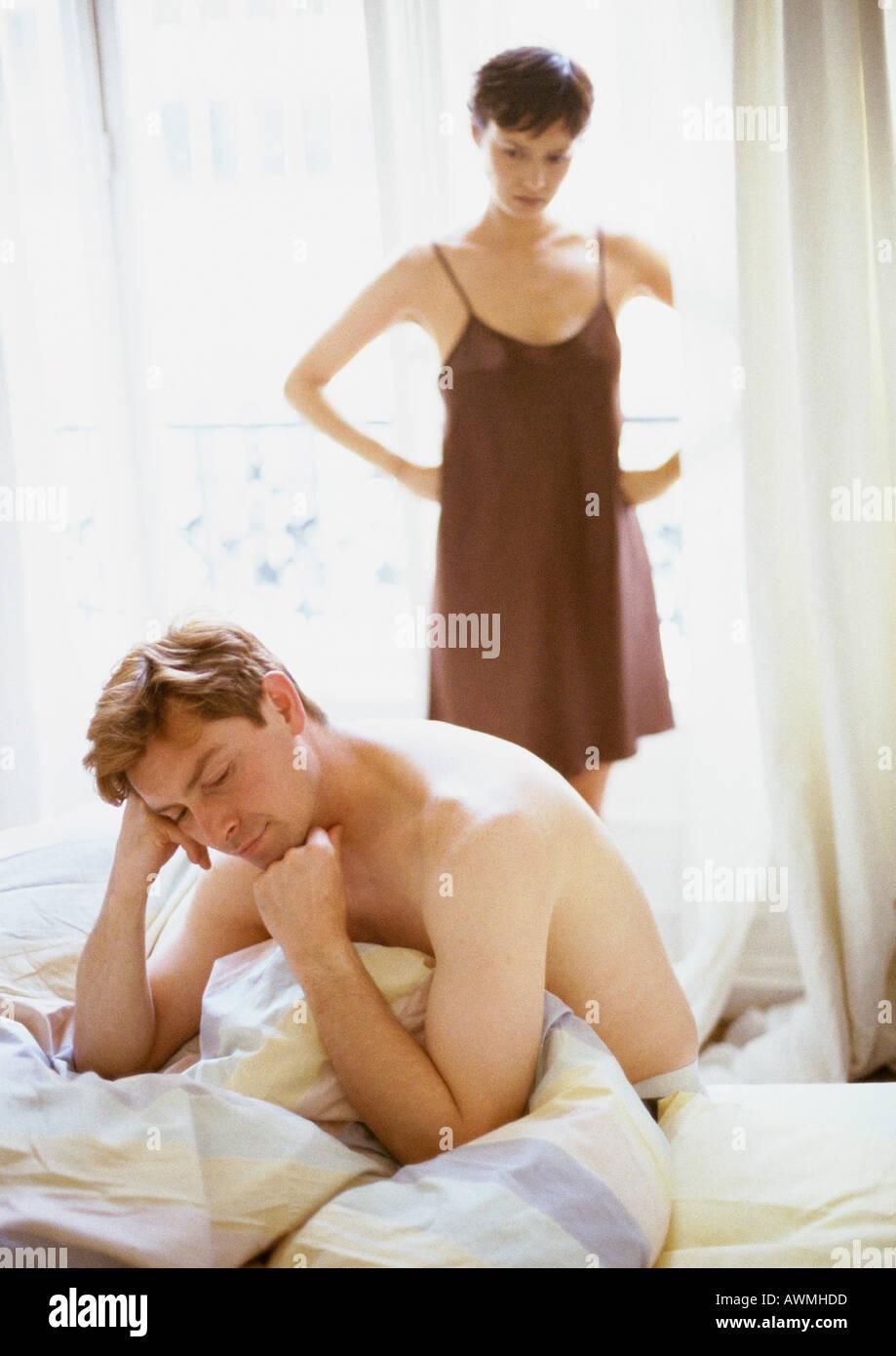 Homme assis sur lit, femme debout avec les mains sur les hanches en arrière-plan Banque D'Images