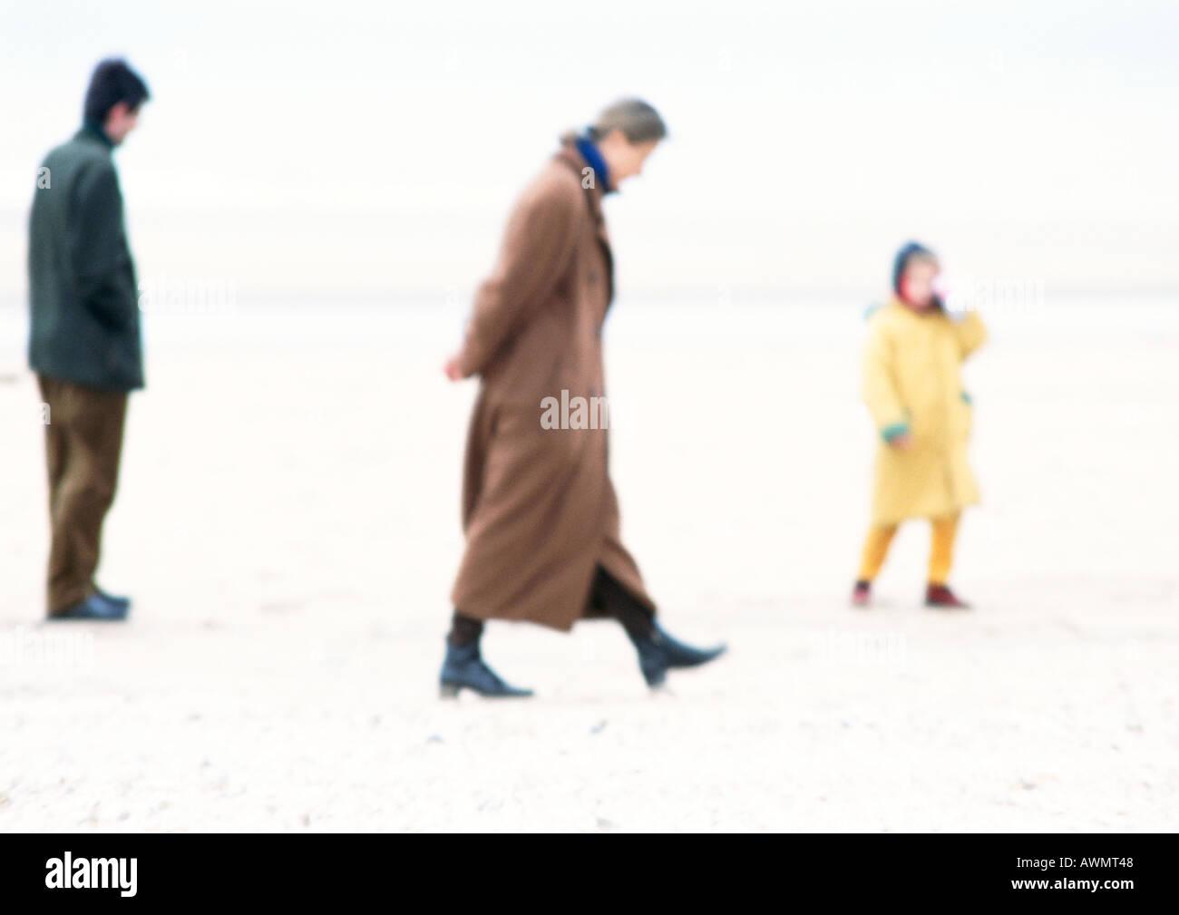 Les gens en manteaux walking on beach, blurred Banque D'Images