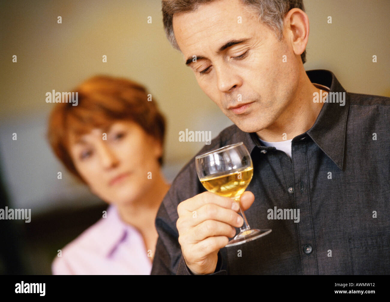 Man holding et à la recherche à un verre de vin, femme floue en arrière-plan, la tête et les épaules, close-up Banque D'Images