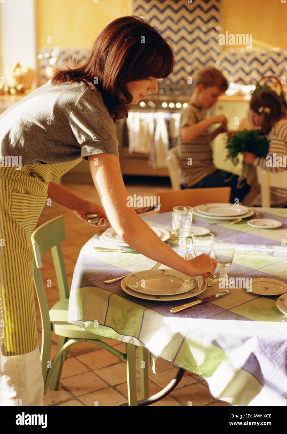 Femme mettent la table, des enfants assis en arrière-plan Photo Stock