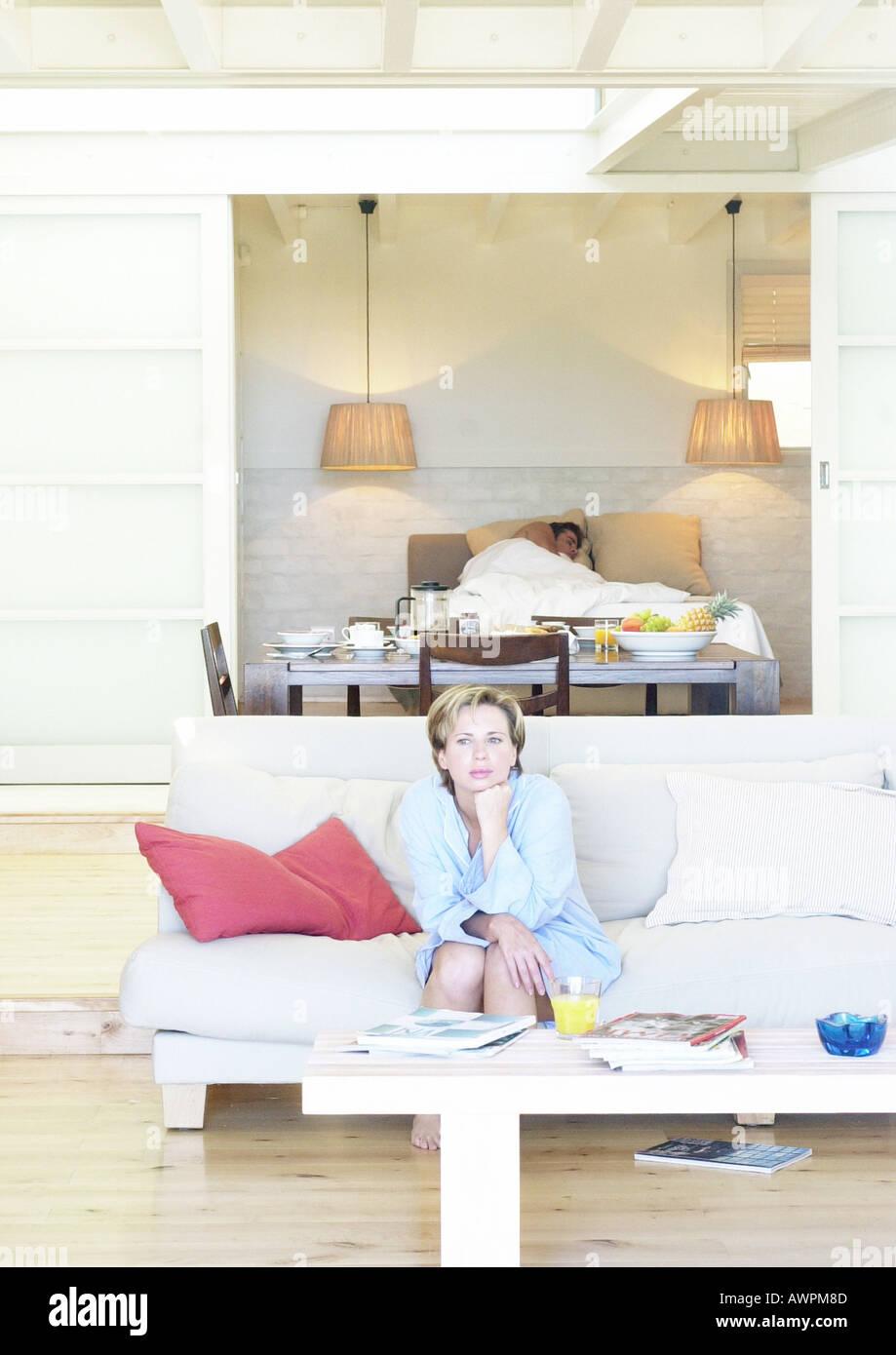 Femme assise sur un canapé, l'homme au lit en arrière-plan Banque D'Images