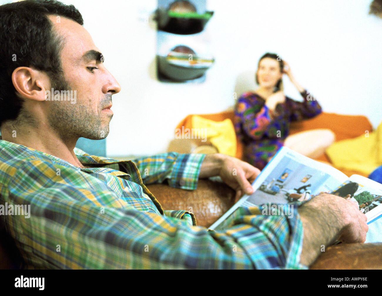 Man reading magazine, femme assise en arrière-plan. Banque D'Images