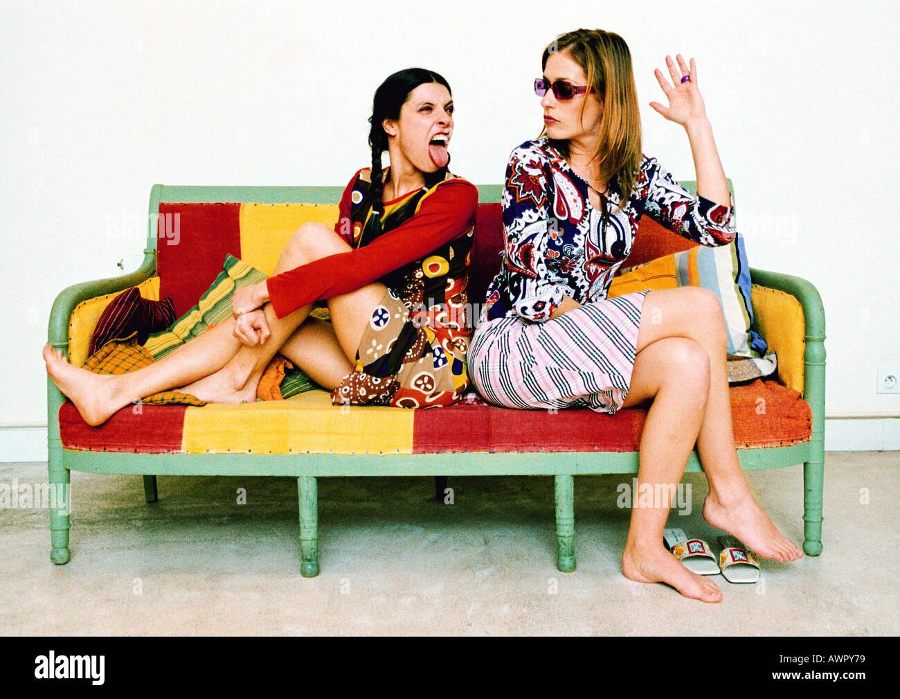 Deux jeunes femmes assises sur un canapé, dos à dos, l'un poussant l'autre à la langue. Banque D'Images