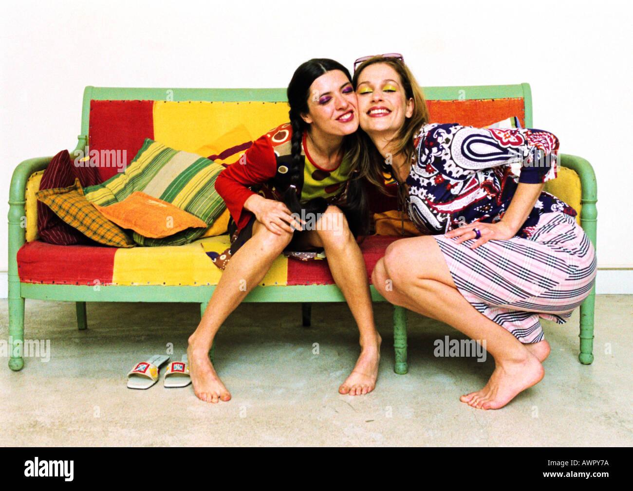 Deux jeunes femmes sur le canapé, joue contre joue, en souriant. Banque D'Images