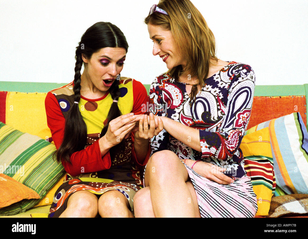 Deux jeunes femmes assises sur un canapé, l'un montrant un autre côté. Banque D'Images