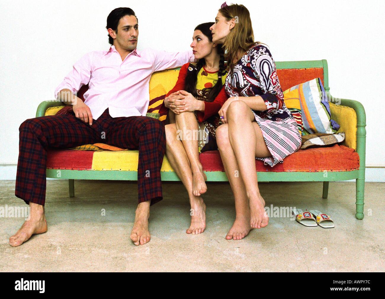 Homme assis sur le canapé avec les jambes écartées, deux femmes assises à côté de lui avec les jambes croisées Banque D'Images