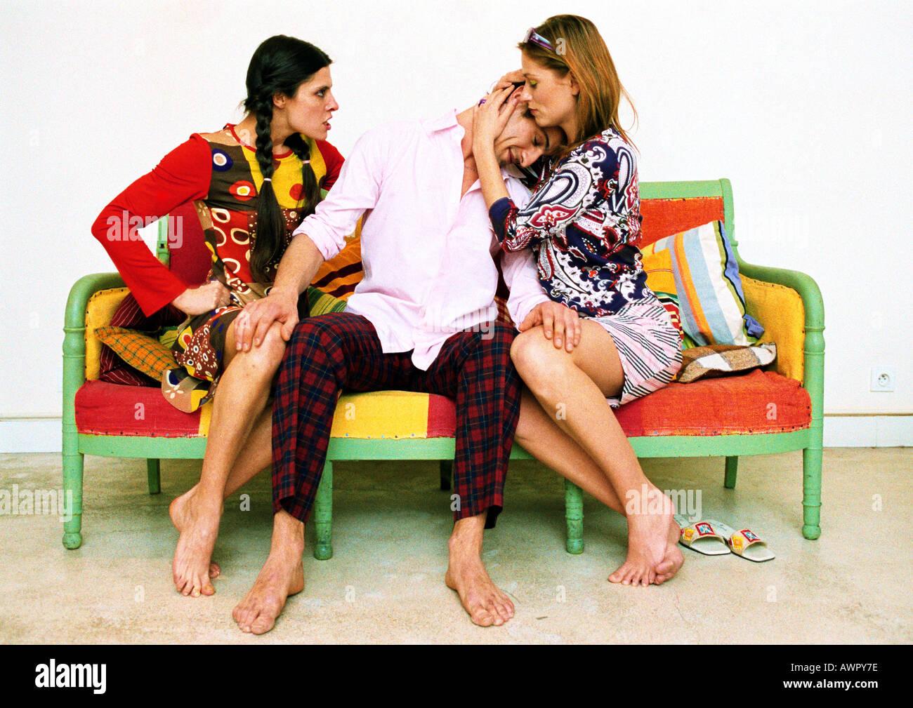 Deux femmes et l'homme sur un canapé, la tête posée sur l'épaule d'une femme, d'autres femme malheureuse. Banque D'Images