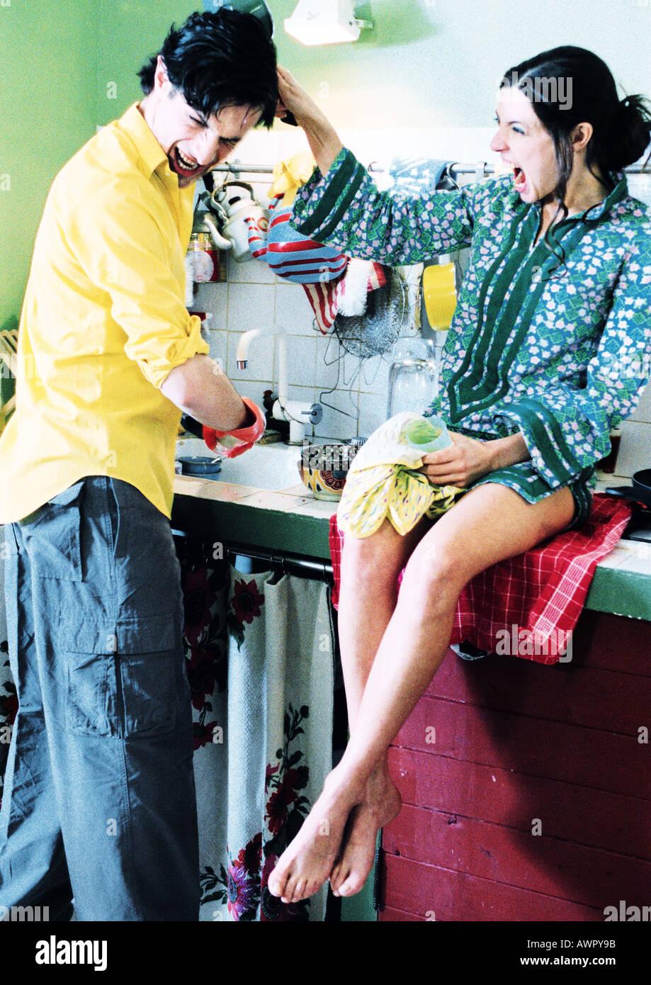 Couple dans la cuisine, l'homme à faire la vaisselle, femme assise sur le comptoir, tirant les cheveux de l'homme. Banque D'Images