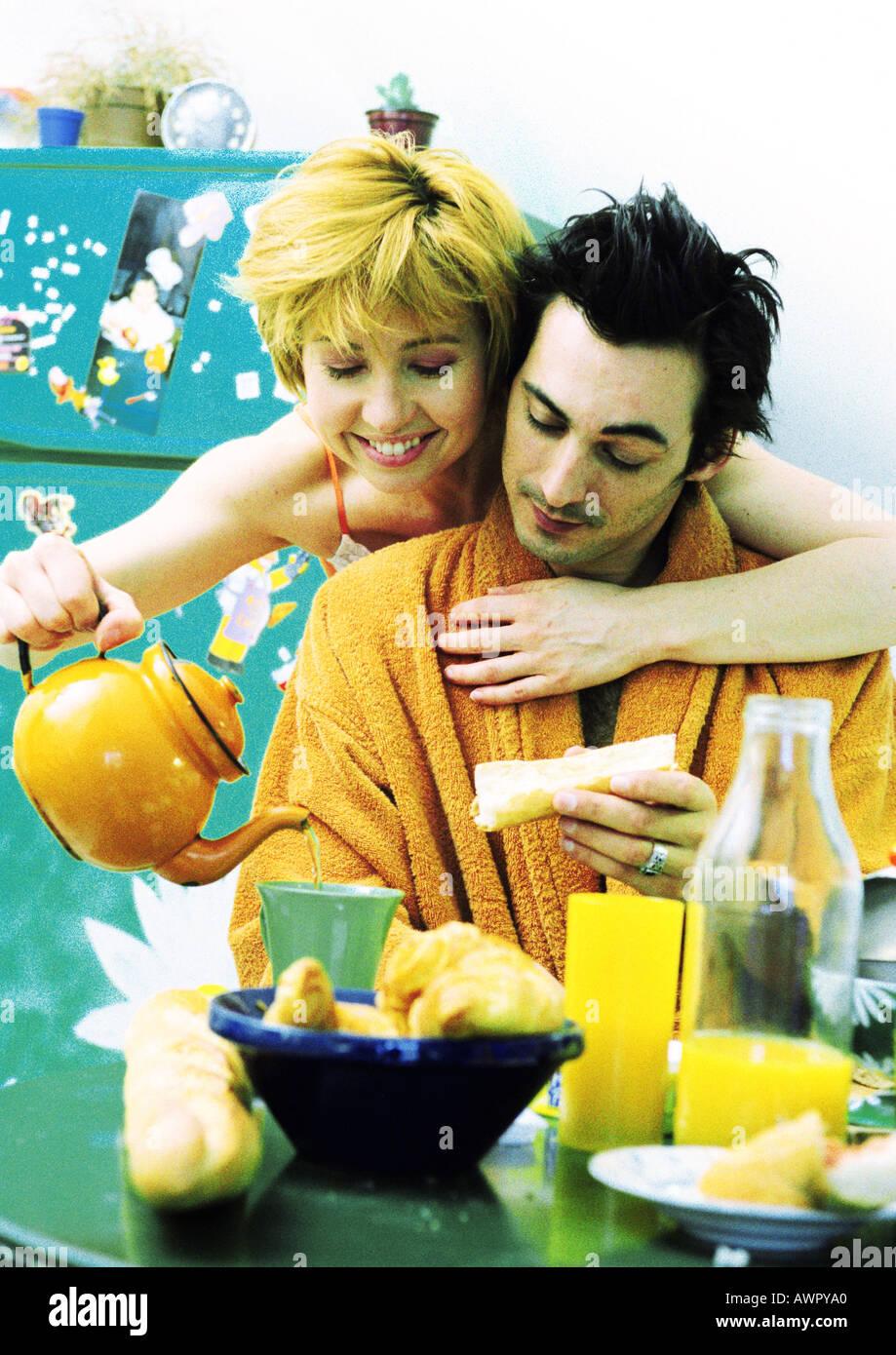 L'homme assis à table de petit déjeuner, la femme à bras autour de l'homme, verser le thé. Banque D'Images