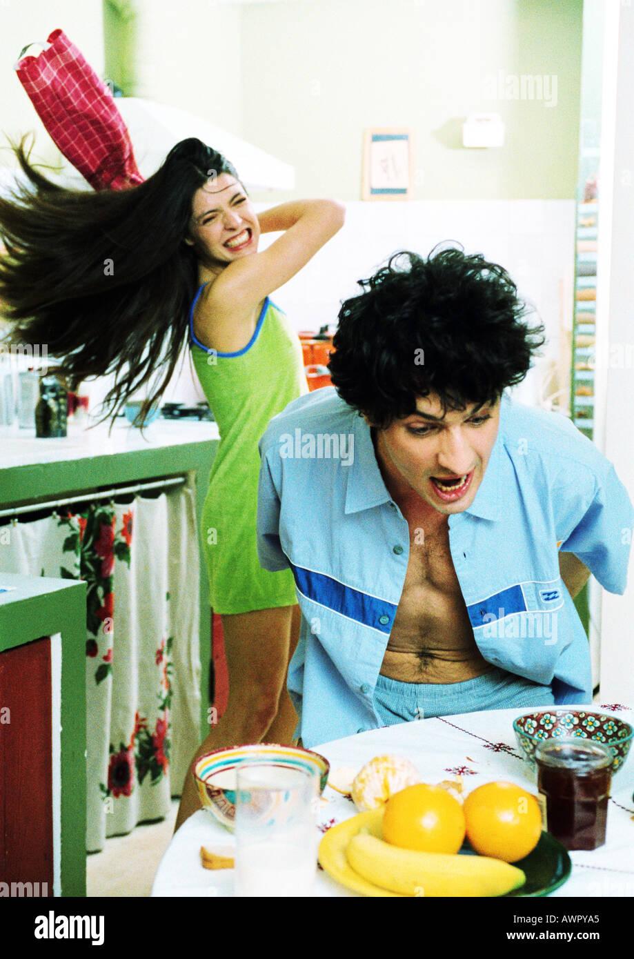 L'homme à table de petit déjeuner, cuisine oscillante femme serviette à l'homme. Banque D'Images