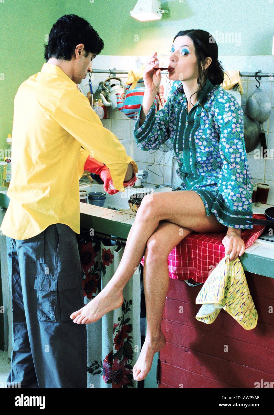 Couple dans la cuisine, l'homme à faire la vaisselle, femme assise sur le comptoir, l'alcool Banque D'Images