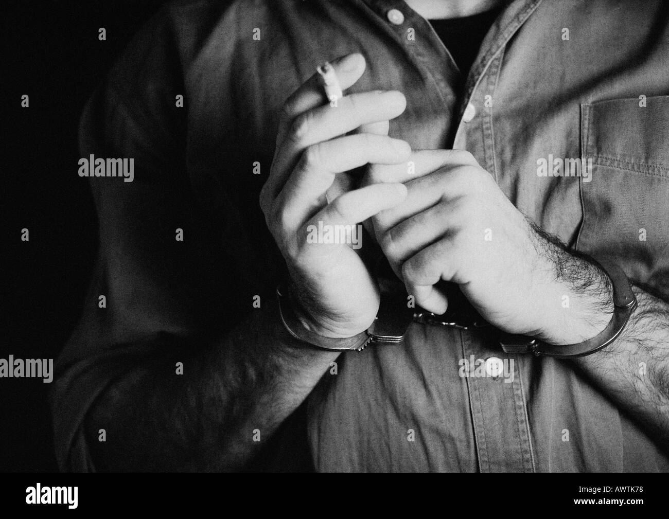 Homme portant des menottes et holding cigarette, close-up, b&w Photo Stock