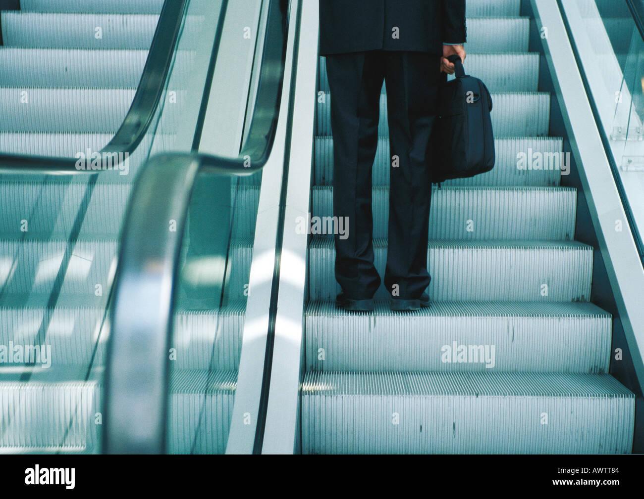 Businessman on escalator, partie inférieure Photo Stock