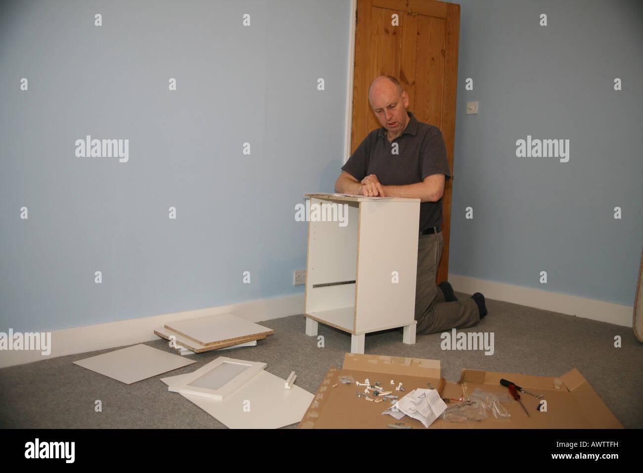 La lecture de l'homme à l'assemblage d'instructions ont acheté des meubles d'Ikea Banque D'Images