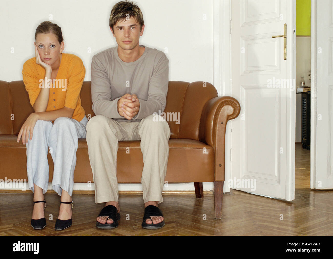 L'homme et la femme assis côte à côte sur le canapé Banque D'Images