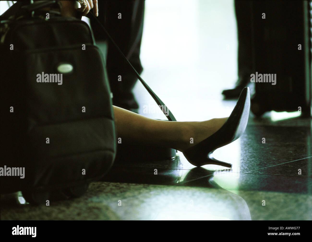 Woman's foot et valise sur le plancher. Photo Stock