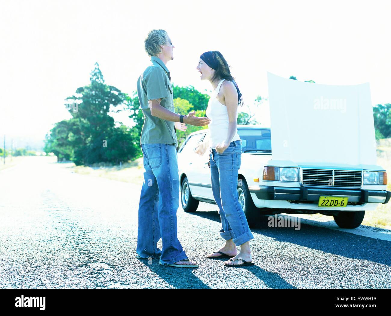 L'homme et la femme debout devant de voiture avec le capot ouvert Banque D'Images
