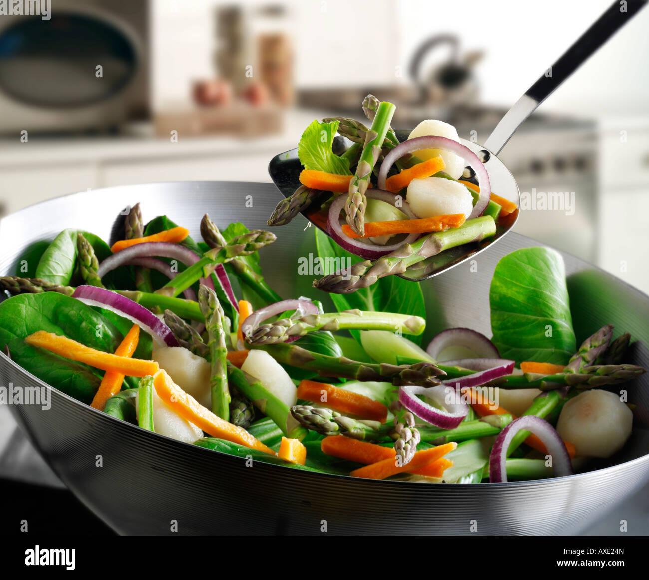 Sauté de légumes au wok étant brassé avec les asperges, les oignons rouges, les pousses de haricot, pak choi et Banque D'Images