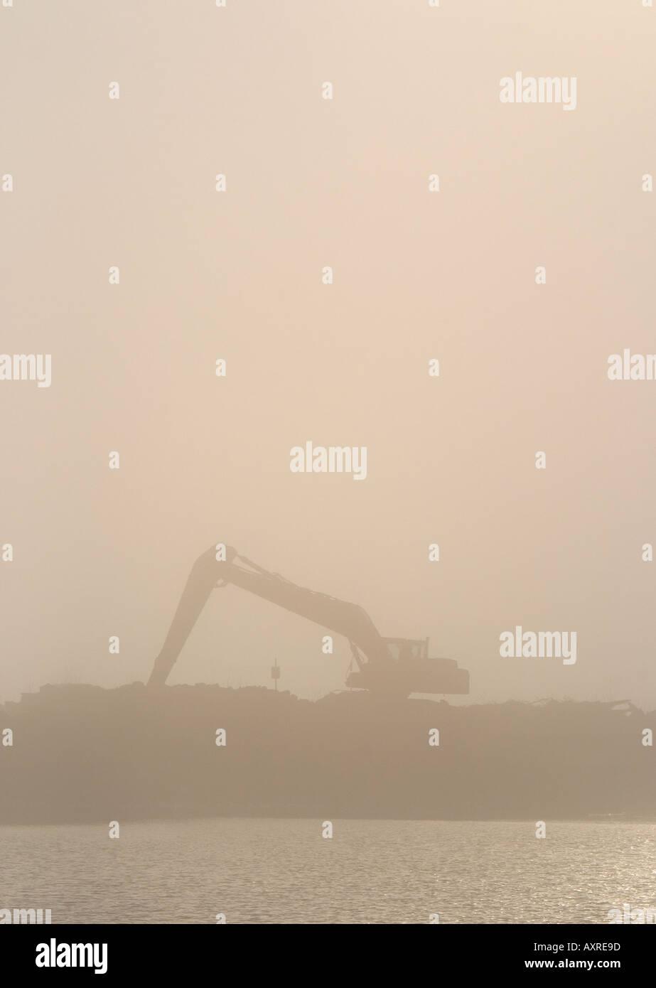 Digger silhouette en matin brouillard à berge , Finlande Photo Stock
