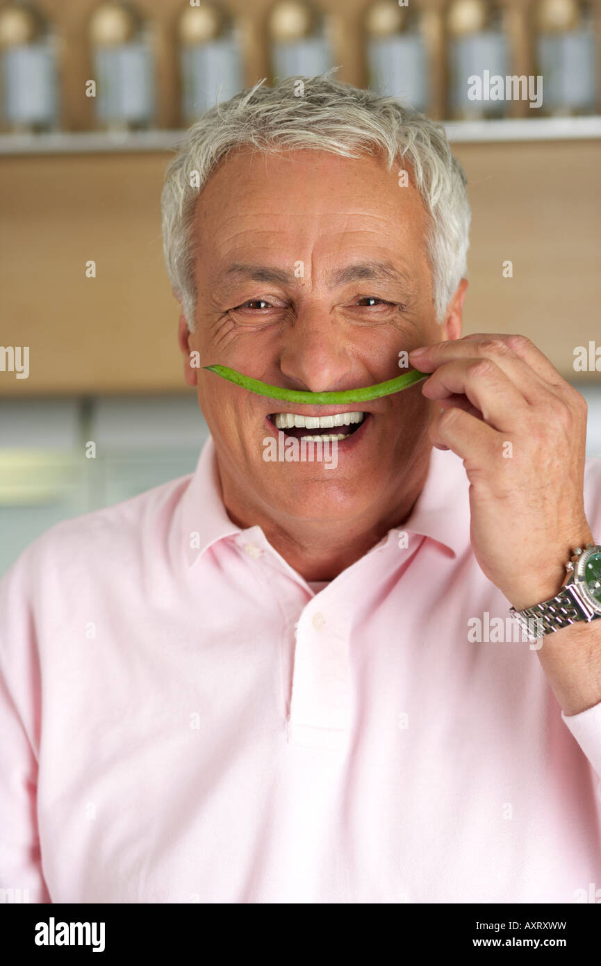 Homme aux cheveux gris tenant un haricot vert sous son nez, close-up Photo Stock