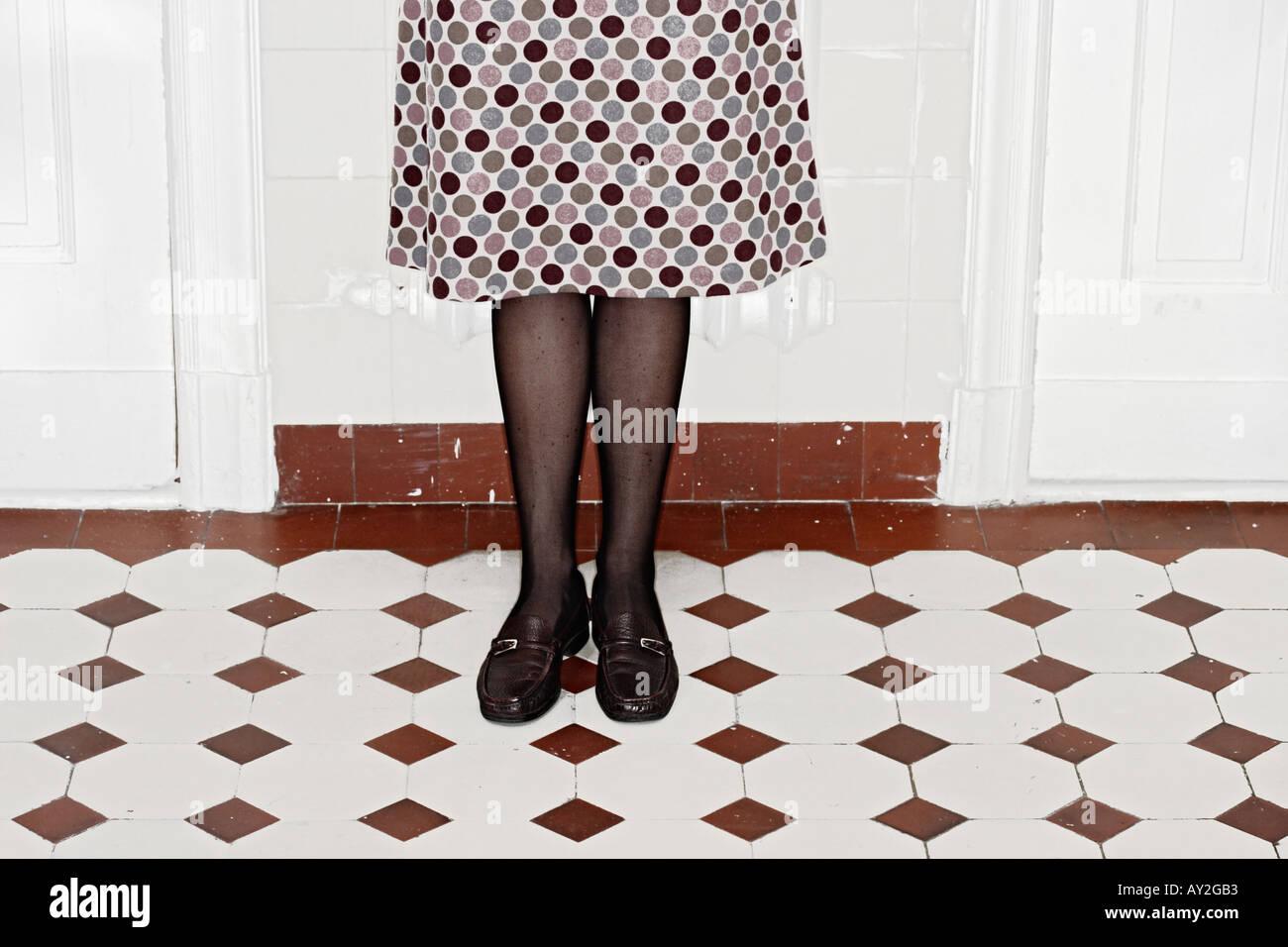 Jeune femme en jupe en pointillé sur les carreaux permanent En Vacances Berlin Allemagne Photo Stock