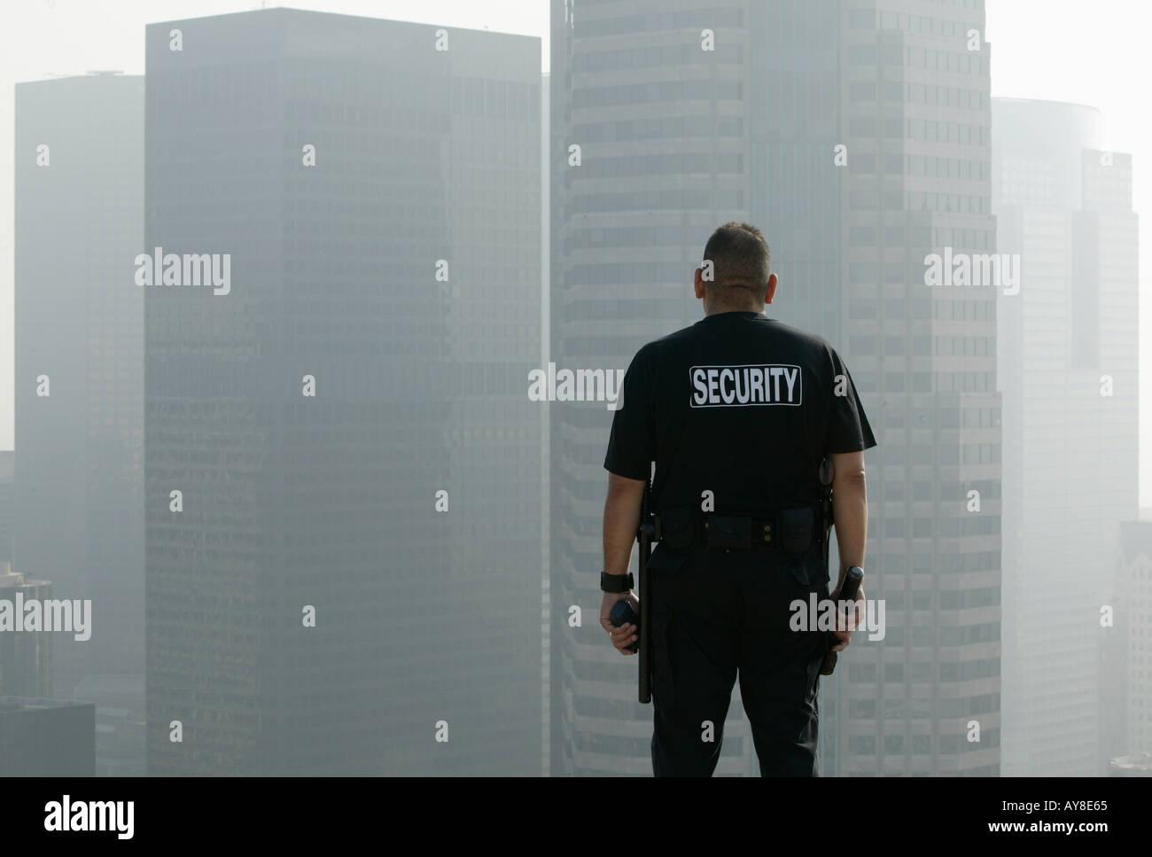 92b199adc63b6 Agent de sécurité se tient sur le toit de l'immeuble de bureaux de grande  hauteur donnant sur d'autres édifices du centre-ville de Los Angeles, CA