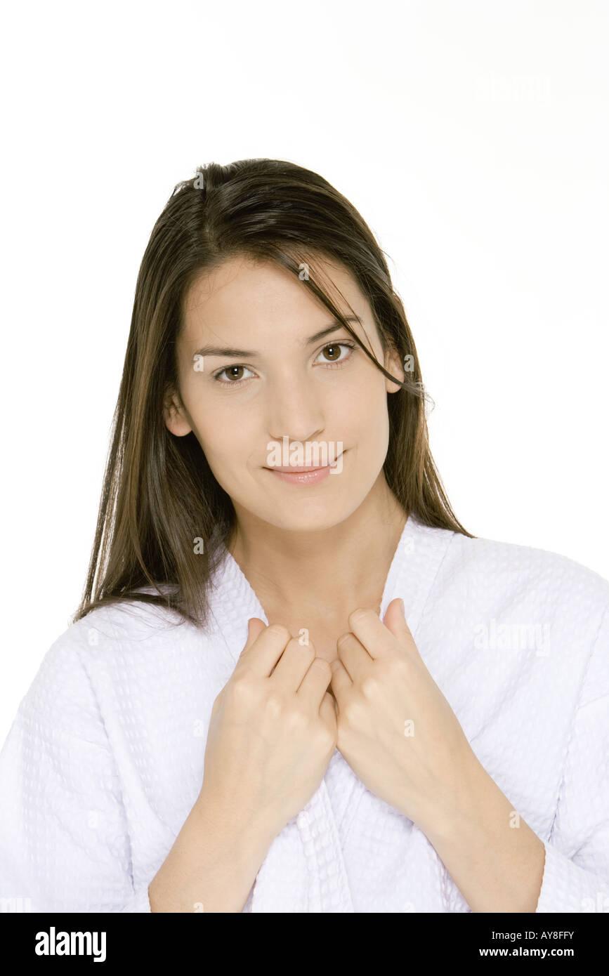 Woman wearing bathrobe, la maintenant sur les bords du col, smiling at camera Banque D'Images