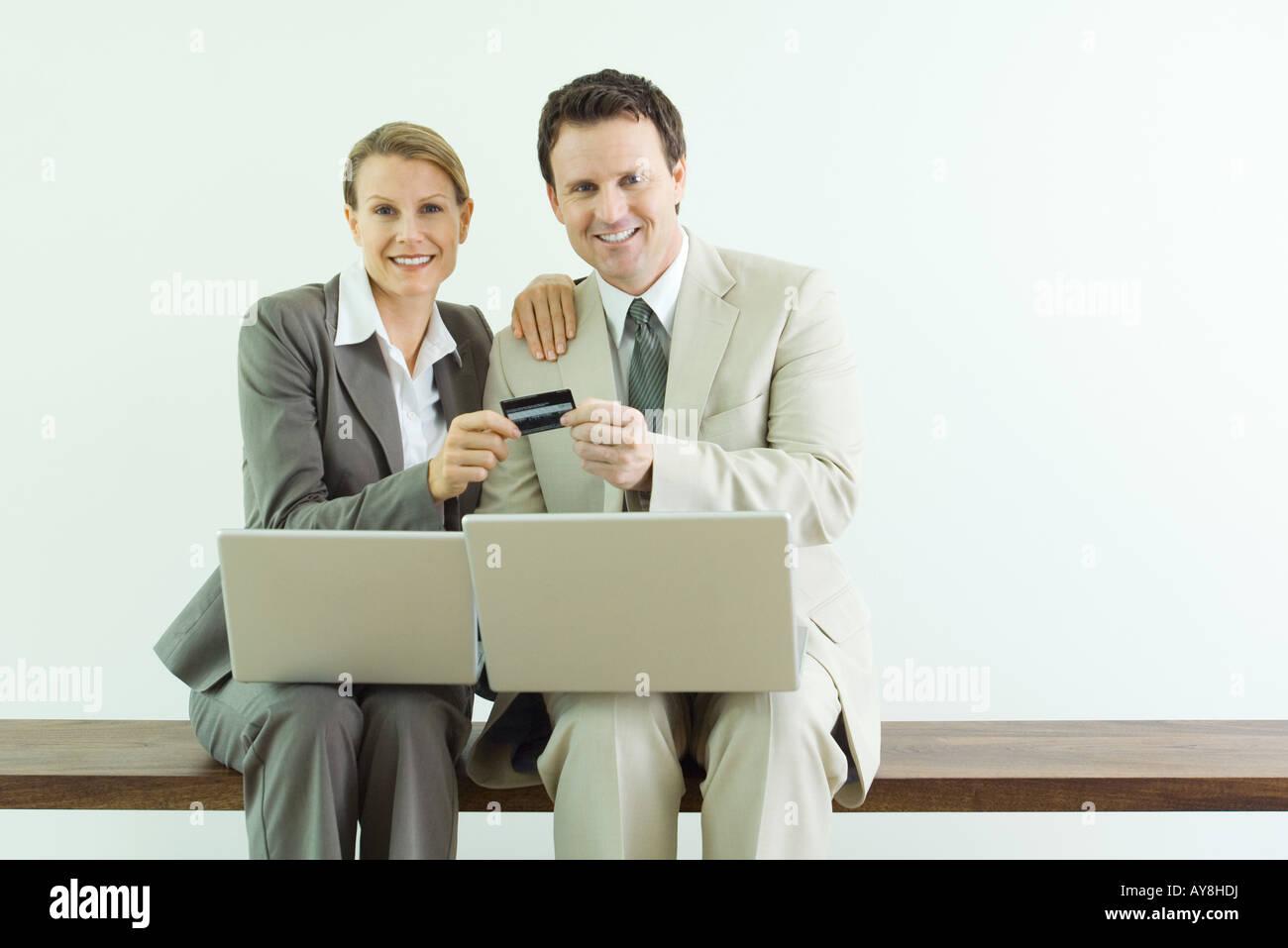 Homme et femme assise, holding credit card ensemble, les deux habillés en costumes d'ordinateurs portables Photo Stock