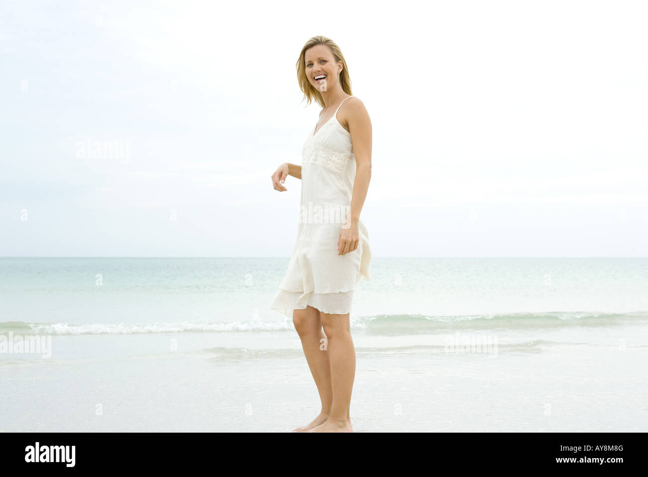 Young woman standing on beach in sundress, rire Photo Stock