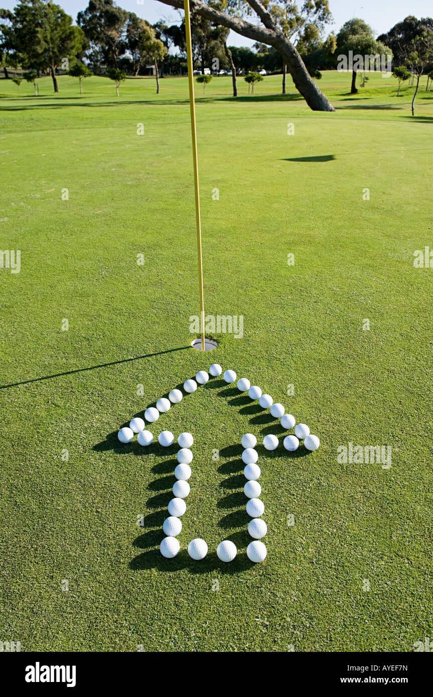 Une flèche pointant vers un trou sur un vert de golf Photo Stock