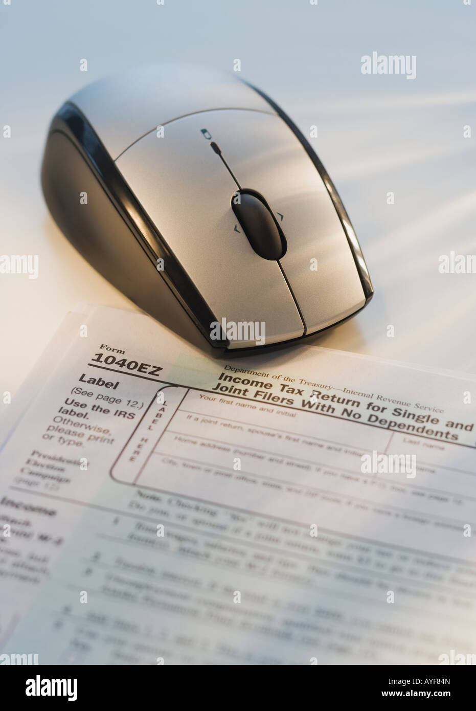 Souris d'ordinateur à côté de formulaire d'impôt Photo Stock