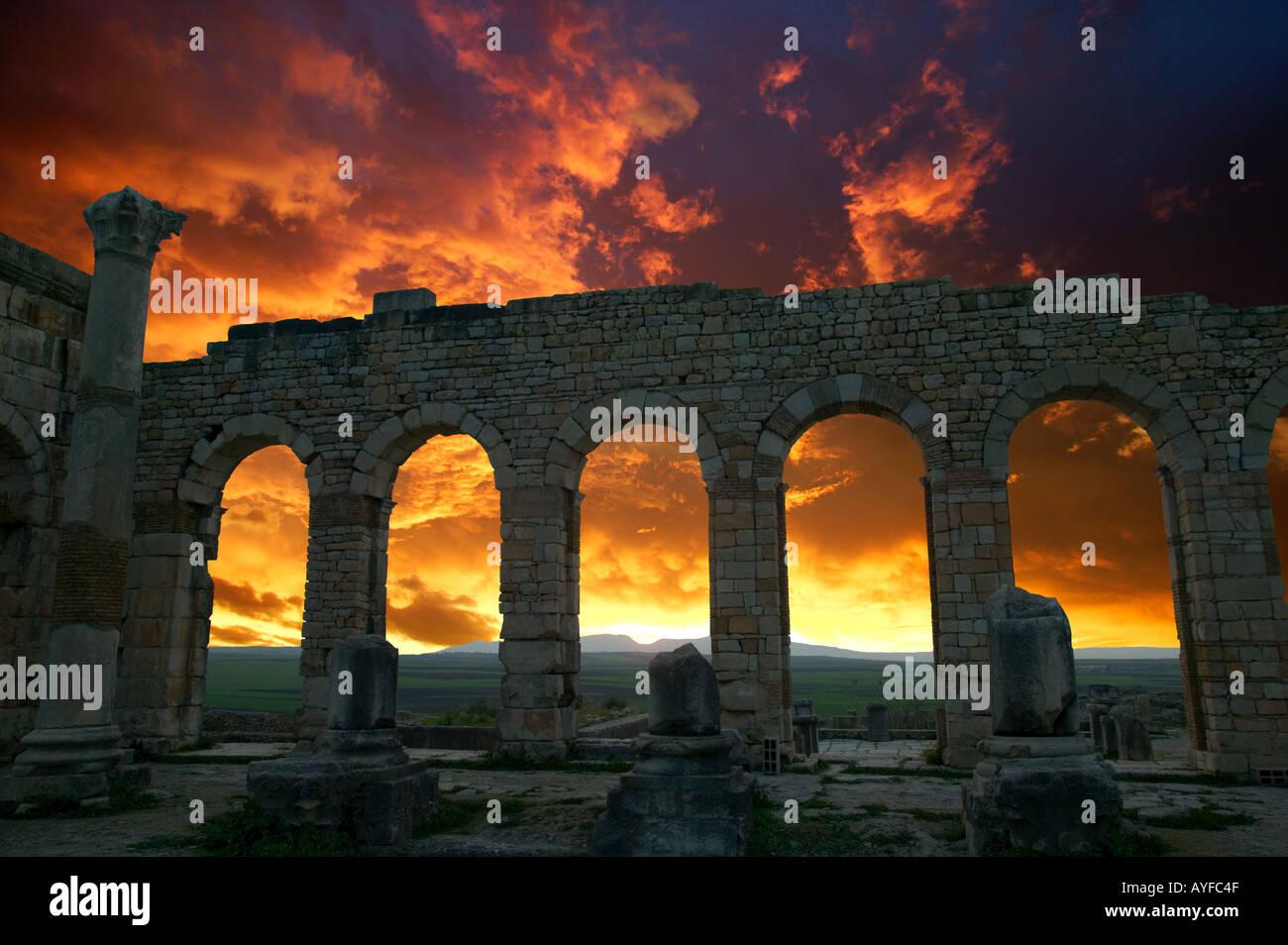 Les ruines romaines de Volubilis date du 2e et 3e siècles les silhouettes au coucher du soleil de la basilique d'arcades - Maroc Photo Stock