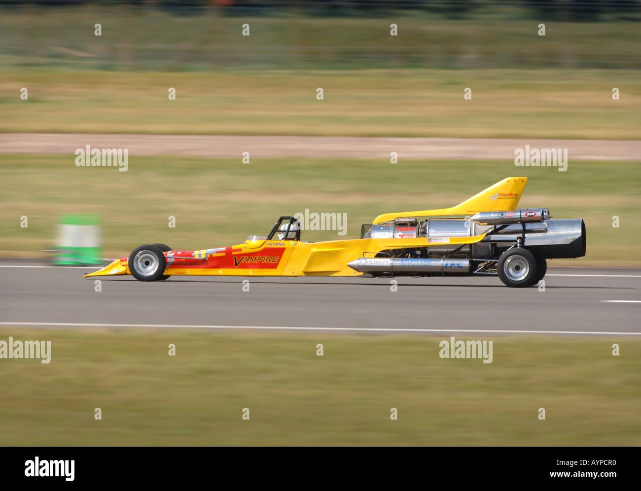 La British Land Speed Record de tenter l'ESSAI PILOTE COLIN JACHÈRES LA VOITURE À JET VAMPIRE AFTERBURNING RAF FAIRFORD Photo Stock